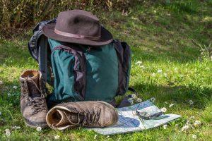 Rucksack mit Wanderschuhen, Karte und Kompass